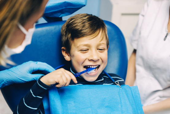 young boy at the dentist practicing brushing